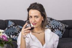 Härlig kvinna som dricker vinsammanträde på en soffa Royaltyfria Bilder