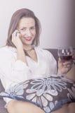 Härlig kvinna som dricker vinsammanträde på en soffa Arkivfoton