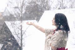 Härlig kvinna som fångar snöflingor arkivfoto