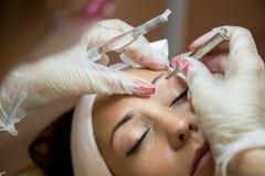 Härlig kvinna som får hennes ögonbryn gjorda på en skönhetsalong fotografering för bildbyråer