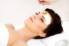 Härlig kvinna som får Spa behandling. Kosmetisk maskering på framsida. Arkivfoton