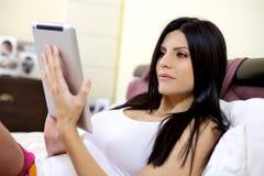 Härlig kvinna som fungerar med tabletipad i underlag Arkivbild