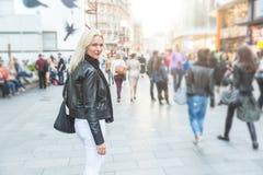 Härlig kvinna som går i den fullsatta London gatan Arkivbild