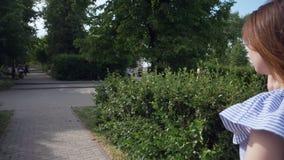 Härlig kvinna som går i parkera och talar på telefonen lager videofilmer