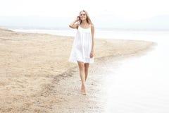 Härlig kvinna som går på stranden som tycker om sommar Arkivfoton