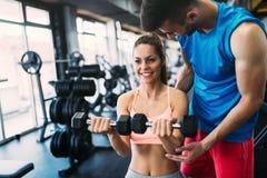 Härlig kvinna som gör övningar i idrottshall med den personliga instruktören Royaltyfri Bild