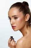 Härlig kvinna som gör makeup genom att använda kantglans på kanter Skönhetsmedel Arkivfoton