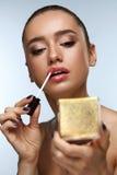 Härlig kvinna som gör makeup som sätter Lipgloss på kanter Skönhetsmedel Arkivbild
