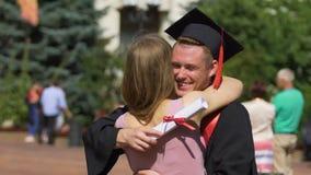 Härlig kvinna som gratulerar pojkvännen på avläggandet av examen, lyckligt krama för par lager videofilmer