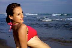 Härlig kvinna som håller ögonen på det wild havet Royaltyfria Bilder