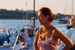 Härlig kvinna som håller ögonen på solnedgången som står på bakgrunden av yachter Royaltyfri Bild