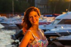 Härlig kvinna som håller ögonen på solnedgången som står på bakgrunden av yachter Royaltyfri Foto