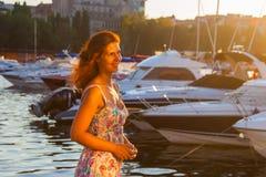 Härlig kvinna som håller ögonen på solnedgången som står på bakgrunden av yachter Arkivfoton