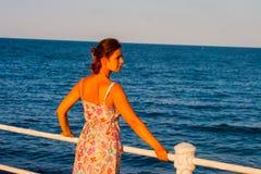 Härlig kvinna som håller ögonen på solnedgången som står på stranden Royaltyfri Fotografi