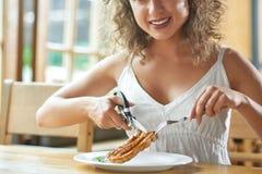Härlig kvinna som har lunch på restaurangen Arkivfoto