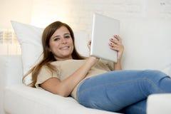Härlig kvinna som hemma ler lyckligt funktionsdugligt med det digitala minnestavladatorblocket Royaltyfri Fotografi