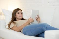 Härlig kvinna som hemma ler lyckligt funktionsdugligt med det digitala minnestavladatorblocket Arkivfoto