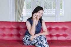 Härlig kvinna som hemma talar på en telefon arkivbilder