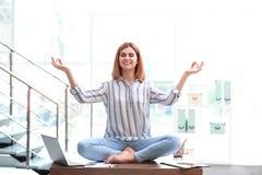 Härlig kvinna som i regeringsställning mediterar på tabellen under avbrott arkivbild
