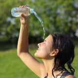 Härlig kvinna som kastar sig vatten från en plast- flaska Royaltyfri Foto