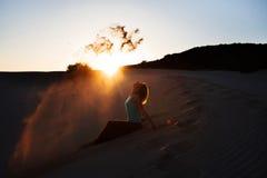 Härlig kvinna som kastas en sand i dyn på solnedgången royaltyfri foto