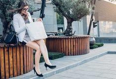 Härlig kvinna som kontrollerar hennes nya saker, når att ha shoppat Royaltyfria Bilder