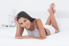 Härlig kvinna som kopplar av att ligga i säng Arkivbilder