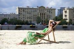 härlig kvinna som kopplar av att ligga på en soldagdrivare Royaltyfri Foto