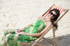 Härlig kvinna som kopplar av att ligga på en soldagdrivare Royaltyfria Foton