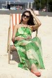 Härlig kvinna som kopplar av att ligga på en soldagdrivare Royaltyfri Fotografi
