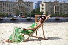 Härlig kvinna som kopplar av att ligga på en soldagdrivare Arkivbilder