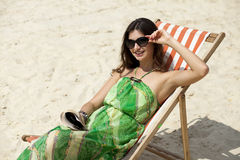 Härlig kvinna som kopplar av att ligga på en soldagdrivare Arkivfoton