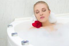 Härlig kvinna som kopplar av i bad med blomman och stearinljus Fotografering för Bildbyråer