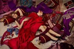 Härlig kvinna som kopplar av på kuddarna i eller Fotografering för Bildbyråer