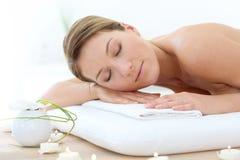 Härlig kvinna som kopplar av på massagesäng Arkivbilder