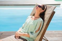 Härlig kvinna som kopplar av på soldagdrivare av simbassängen Royaltyfria Foton