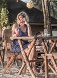 Härlig kvinna som kopplar av på strandrestaurangen Royaltyfri Foto