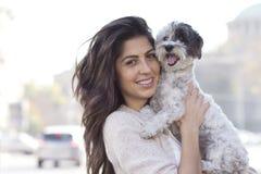 Härlig kvinna som kramar hennes utomhus- lilla hund Royaltyfria Bilder