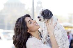 Härlig kvinna som kramar hennes utomhus- lilla hund Arkivfoto