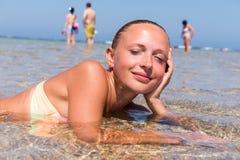 Härlig kvinna som lägger i havet Fotografering för Bildbyråer