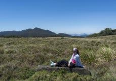 Härlig kvinna som lägger på bänken på nationalparken arkivfoto