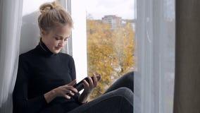 Härlig kvinna som läser en bok i e-avläsare sammanträde på en fönsterbräda arkivfilmer