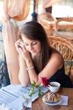 Härlig kvinna som läser en tidning i kafét Arkivbilder