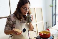 Härlig kvinna som lagar mat och luktar de trevliga aromerna från kryddor i en kruka i organiskt lager royaltyfri foto