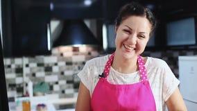 Härlig kvinna som ler i kök stock video
