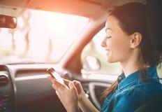 Härlig kvinna som ler, medan sitta på de främre passagerareplatserna i bilen Flickan använder en smartphone royaltyfri foto
