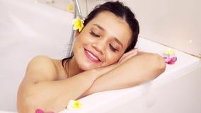 Härlig kvinna som ler på kameran i badkar lager videofilmer