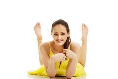 Härlig kvinna som ligger i gul klänning Arkivbilder