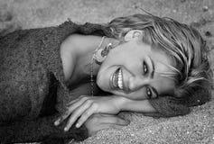 Härlig kvinna som ligger i stenarna Arkivfoto