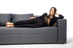 Härlig kvinna som ligger på en vit soffa som isoleras på vit royaltyfria bilder